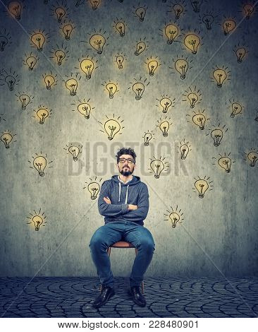Young Hipster Man Contemplating And Looking Up Creating Idea While Sitting On Chair.