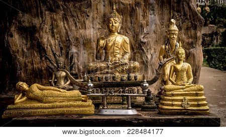 Various Buddha Statues In The Temple Of Thailand. Buddha Sits, Buddha Lies. Wooden Background