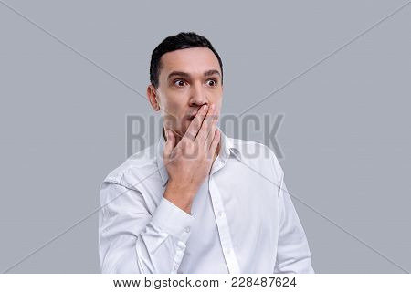 Baffled. Attractive Amazed Dark-eyed Young Man Wearing A White Shirt And Having His Eyes Wide-opened