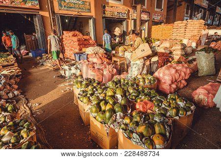 Dambulla, Sri Lanka - Jan 7, 2017: Buyers Walking Around Fruit Market Stands And Bags Of Pineapple,