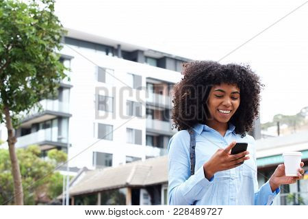 African American Girl Walking With Cell Phone Outside In The City