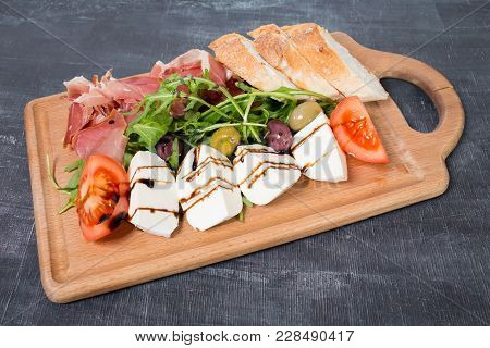 Starter Platter With Prosciutto Crudo And Fresh Vegetables. Plate Located On A Black Table As A Back