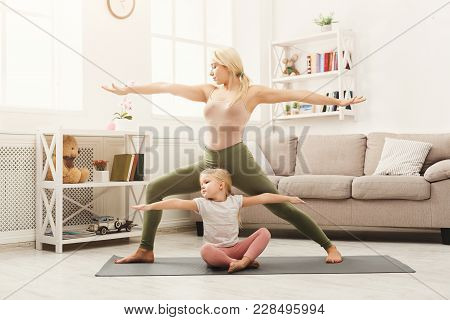 Young Mother Showing Her Little Daughter Yoga Poses. Happy Girls Training At Home. Motherhood And Sp