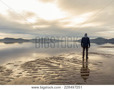 Man Standing At The Beach In The Norwegian Fjord Tovdalsfjorden, Looking At The Calm Sea And The Mis