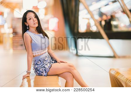 Portrait Of Young Beautiful Asian Girl Sitting At Shopping Mall Or Department Store With Copy Space.