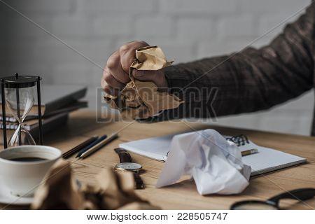 Cropped Shot Of Writer Crumpling Paper At Workplace
