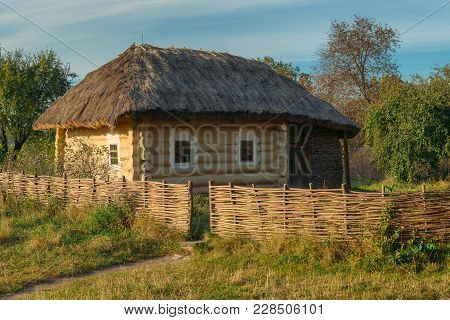 Old East European Rural Wood House With Wattle Fence And Thatched Roof
