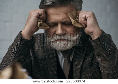 Depressed Senior Man With Crumpled Papers In Hands