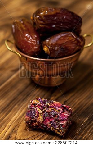 Close Up With Middle Eastern Desserts With Rose Petals And Dates In A Small Copper Cup