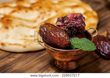 Close Up With Dates And Middle Eastern Desserts With Rose Petals In A Small Copper Cup