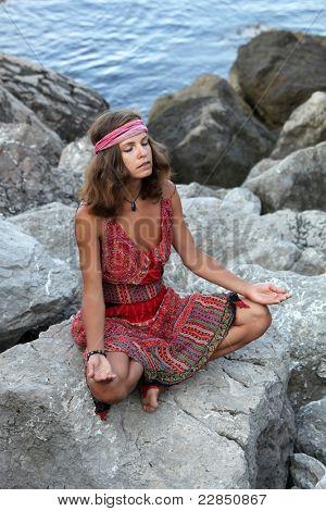 Girl meditating on the rock
