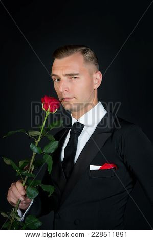 Valentines Day Concept. Man With Red Rose On Dark Background. Ballroom Dancer In Suit With Flower. L