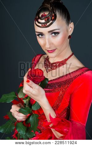 Sensual Woman With Rose On Dark Background. Ballroom Dancer In Red Dress With Flower. Fashion, Beaut