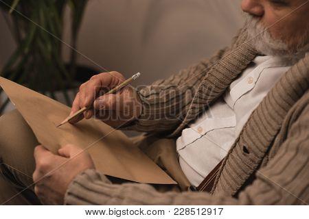 Close-up Shot Of Bearded Senior Man Writing Letter