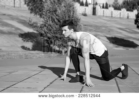 Man Runner At Starting Position. Athlete On Asphalt Path On Sunny Summer Day Outdoors. Fit Macho In