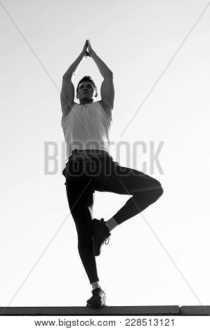 Bodybuilder Man In Tracksuit Posing On Sunny Day On Clear Sky Outdoors. Athlete Model With Strong Mu