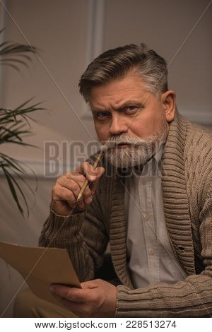 Thoughtful Senior Man Writing Letter And Looking At Camera