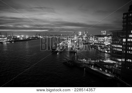 Sea Port With Ships And Cranes In Hamburg, Germany With Light Illumination At Night. Harbor Or Dock