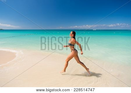 Woman In Bikini Run On Beach In Antigua. Girl In Turquoise Sea Or Ocean Water On Sunny Day. Summer V