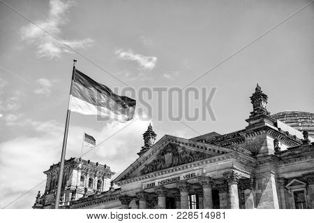 German Flags Waving In The Wind At Famous Reichstag Building, Seat Of The German Parliament (deutsch
