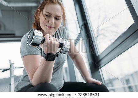 Curvy girl training biceps with dumbbell in gym poster