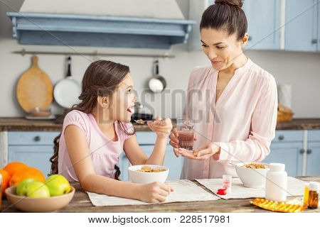 Great Day. Beautiful Exuberant Dark-haired Young Mother Smiling And Giving Vitamins To Her Daughter
