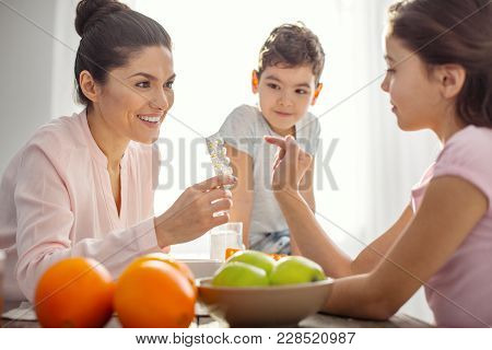 Great Vitamins. Nice Exuberant Dark-haired Young Mother Holding Vitamins And Talking With Her Kids A