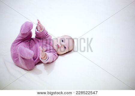Beautiful Child Playing With His Legs On The Bed In Bedroom.