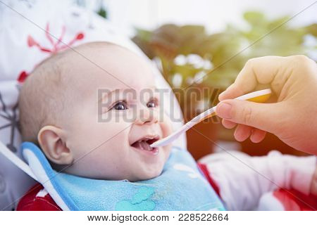 A Child Eat With Spoon At The Table. Happy And Emotional.