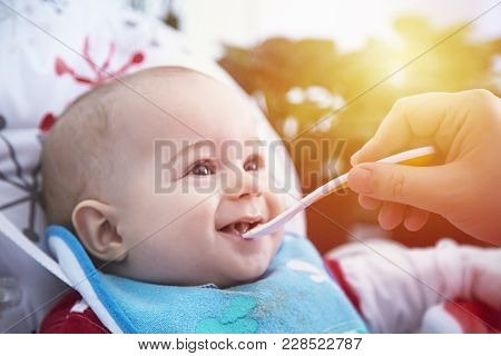 Adorable Baby Have Lunch With Spoon At The Table.