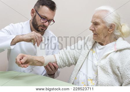 Doctor With A Beard And Glasses Bandages The Elastic Forearm Of A Very Old Gray Woman With A Bandage