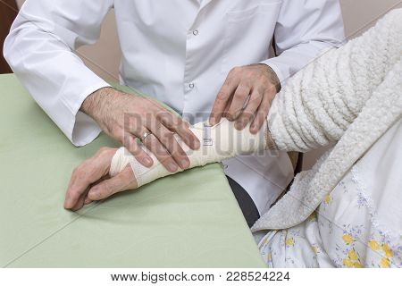 The Doctor Puts On A Bandage With A Flexible Bandage On The Forearm And Wrist Of An Old Woman.