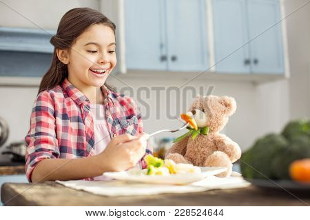 So Appetizing. Beautiful Exuberant Dark-haired Little Girl Smiling And Feeding Her Toy With Healthy