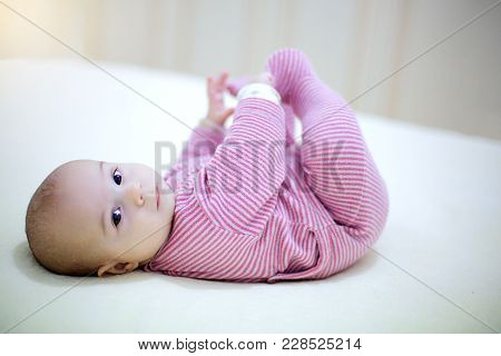 Little Baby Boy Playing With His Legs On The Bed In Bedroom.