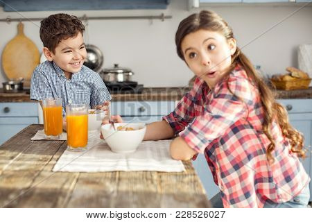 Our Favourite Breakfast. Handsome Exuberant Little Dark-haired Boy Looking At His Sister And Laughin