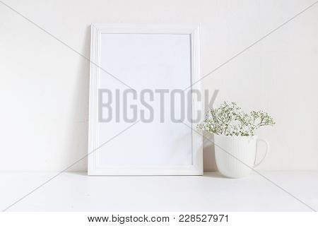 White Blank Wooden Frame Mockup With Baby Breath, Gypsophila Flowers In Porcelain Mug On The Table.