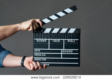 A Movie Production Clapper Board. Hands With A Movie Clapperboard On Grey Background With Copy Space