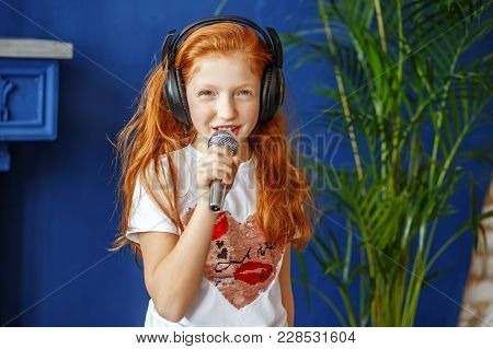 A Red-haired Little Girl Sings A Song. The Concept Is Childhood, Lifestyle, Music, Singing, Listenin