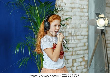 A Red-haired Little Girl Sings A Song In A Microphone. The Concept Is Childhood, Lifestyle, Music, S