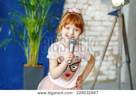 Smiling Child Sings A Song Into The Microphone. The Concept Is Childhood, Lifestyle, Music, Singing,
