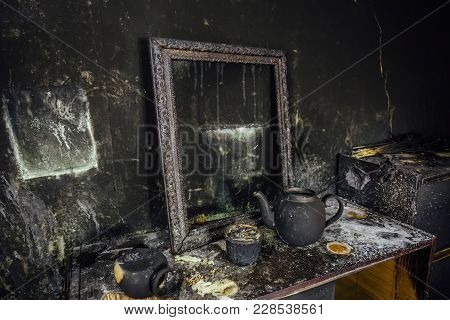 Burnt Room Interior. Burnt Still Life. Charred Wall, Picture Frame, Pot With Burned Rose In Black So