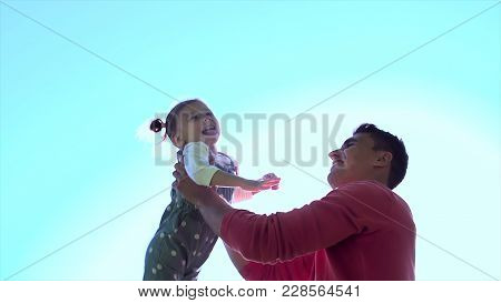 Father Plays With His Daughter Blue Sky Background And Sun Reflection. Father's Day. Happy Joyful Fa