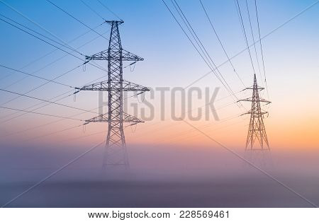 Transmission Towers In The Fog At The Background Of The Dawn Sky. High Voltage Power Line Silhouette