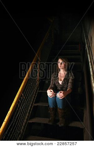 A Young Woman sitting In Shadowy stairs