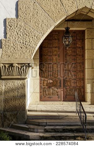 Vertical View Of An Entry With Sandstone Surround And Wrought Iron Railing Leading To A Large Ornate