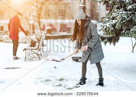 Beautiful Girl In Winter Fashion Clothes With A Shovel Cleans The Snow