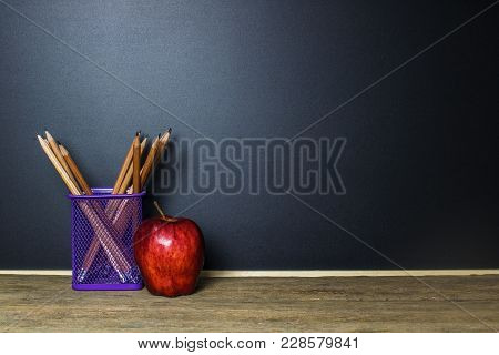 Pencil In Basket And Red Apple On Wood Table With Blackboard (chalk Board) As Background With Copy S