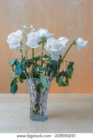 The Plant Is A Bouquet Of White Roses With Green Leaves And Small White Flowers, In A Crystal Vase W