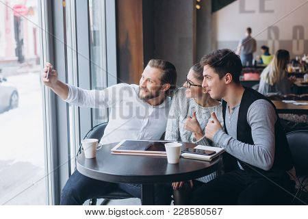 Three Successful Business People Taking A Happy Selfie In The Cafe.