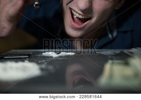 Addict Man Smells Cocaine From A Mirror.
